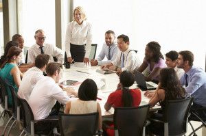31047674 - businesswoman addressing meeting around boardroom table
